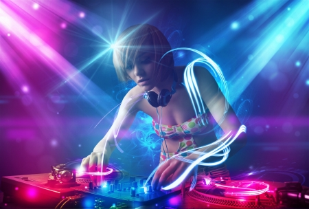 dj mixer: Energetic Dj girl mixing music with powerful light effects Stock Photo