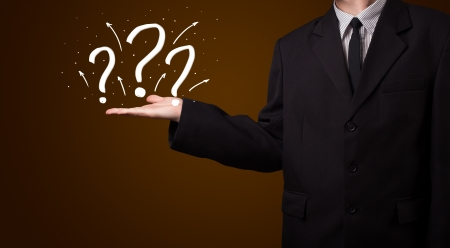 Young business man in suit presenting hand drawn question marks Stock Photo - 22043868