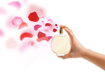 close up of woman hands spraying rose petals from beautiful perfume bottle photo