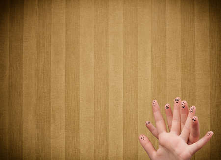 Happy finger smileys faces on hand with vintage stripe wallpaper background photo