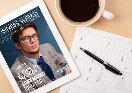 Lugar de trabajo con PC de la tableta que muestra la portada de revista y una taza de café en una mesa de trabajo de madera de cerca Foto de archivo