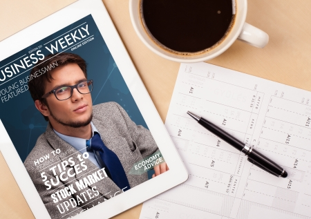 magazine: Workplace with tablet pc showing magazine cover and a cup of coffee on a wooden work table close-up