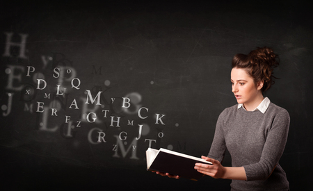 Young lady reading a book with alphabet letters coming out of the book photo