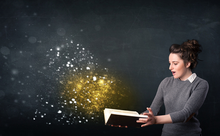 Young lady reading a magical book in front of a blackboard photo