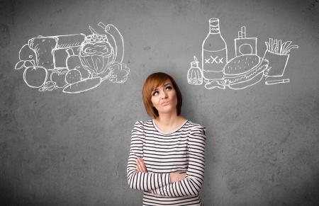 정크 푸드: 꽤 젊은 여자는 건강하고 건강에 해로운 음식 사이의 선택 스톡 사진