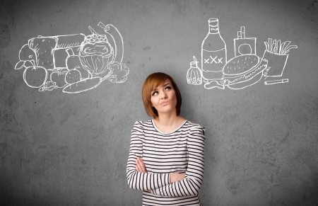 Pretty young woman choosing between healthy and unhealthy foods Stock Photo - 22280789