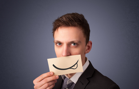 Happy businessman holding funny white card on his mouth with gradient background photo