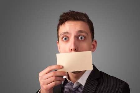 Businessman holding white card at front of her lips with copy space on gradient background Stock Photo - 22280797