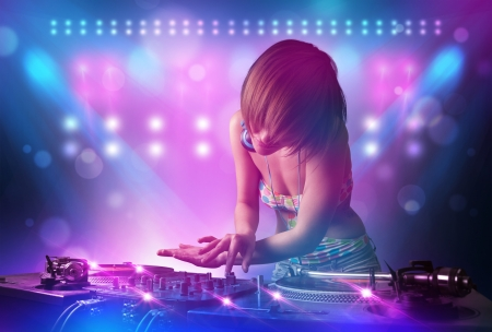 night club: Pretty young disc jockey mixing music on turntables on stage with lights and stroboscopes Stock Photo
