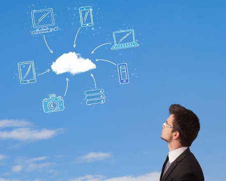 Handsome man looking at cloud computing concept on blue sky photo