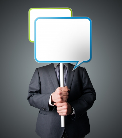 Businessman standing and holding an empty speech bubble in front of his head photo
