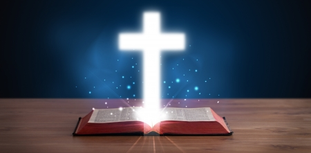 grunge cross: Open holy bible with glowing cross in the middle on wooden deck Stock Photo