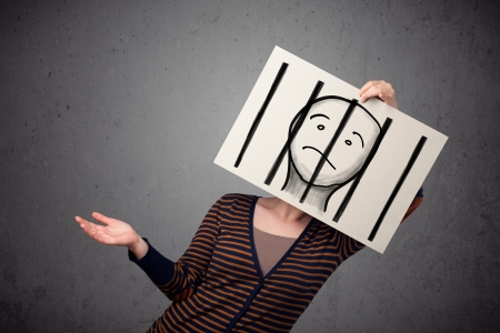Woman holding a paper with a prisoner in jail behind the bars on it in front of her head Stock Photo - 22220691