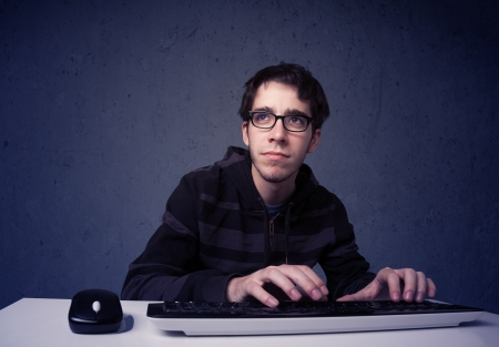 Hacker working with keyboard and mouse on blue background photo