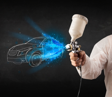 repair shop: Worker with airbrush gun painting hand drawn white car lines Stock Photo