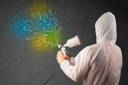 Worker with airbrush gun paints colorful lines and splashes concept photo