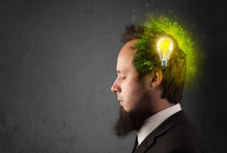 Young mind thinking of green eco energy with lightbulb on grungy background photo