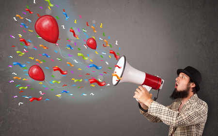 Young guy having fun, shouting into megaphone with balloons and confetti Stock Photo - 22280920