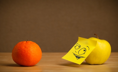 reacting: Apple with sticky post-it note reacting at orange