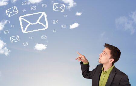 Businessman looking at mail symbol clouds on blue sky