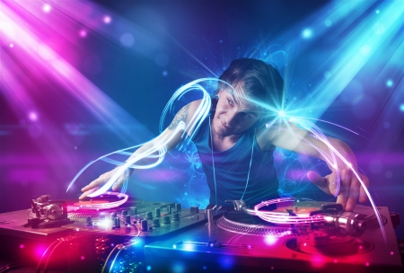 electronic music: Young energetic Dj mixing music with powerful light effects