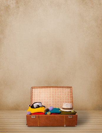 luggage: Retro tourist luggage with colorful clothes and copyspace on grungy background Stock Photo