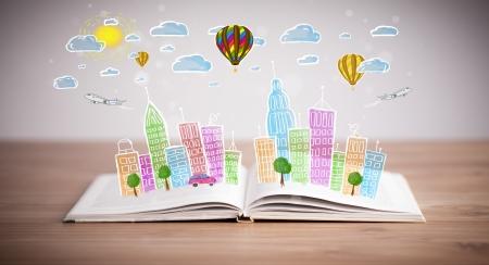 cielos abiertos: Colorido dibujo paisaje urbano en el libro abierto Foto de archivo