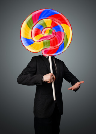 hidden success: Businessman holding a colorful striped lollipop in front of his head