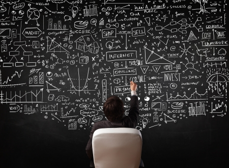 information analysis: Young businessman sitting in office chair in front of a blackboard with sketched charts and signs