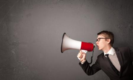 hablar en publico: Chico grita en el meg�fono sobre fondo copia espacio Foto de archivo