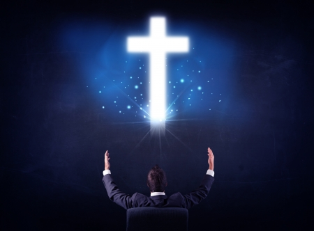 Young businessman sitting in an office chair with glowing cross above his head photo