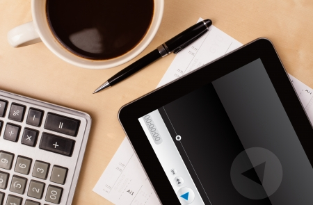 Workplace with tablet pc showing media player and a cup of coffee on a wooden work table close-up photo
