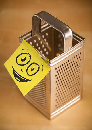 metal grater: Drawn smiley face on a post-it note sticked on a grater Stock Photo