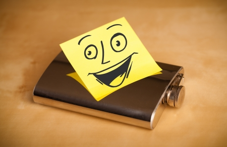 case sheet: Drawn smiley face on a post-it note sticked on a hip flask