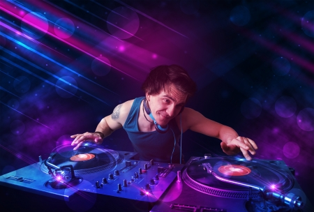 listen to music: Attractive young DJ playing on turntables with color light effects Stock Photo