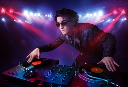 listen to music: Handsome teenager dj mixing records in front of a crowd on stage