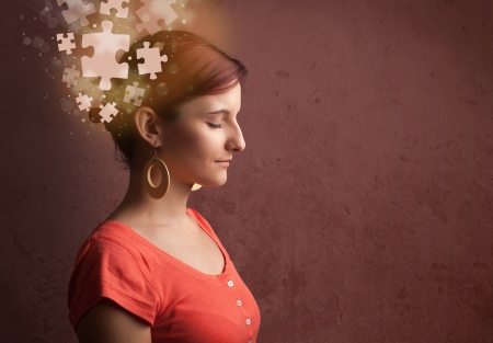 business mind: Young person thinking with glowing puzzle mind on grungy background