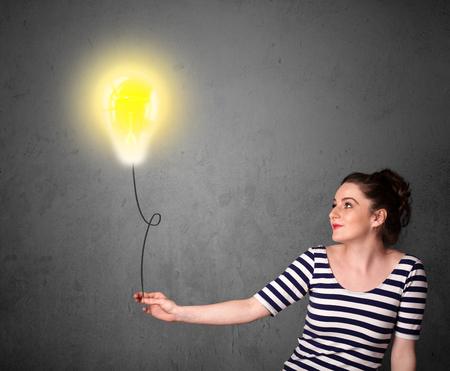 Young woman holding a lightbulb balloon photo