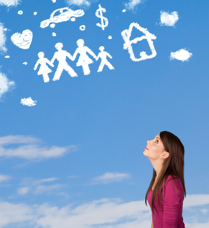 Young girl daydreaming with family and household clouds on blue sky photo