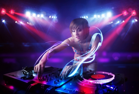 dance and electronic: Pretty young disc jockey girl playing music with light beam effects on stage