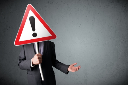 Businessman holding a red traffic triangle warning sign in front of his head Stock Photo - 22649620