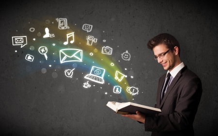 Businessman reading a book with multimedia icons coming out of the book photo