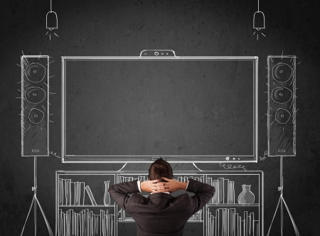 watch: Young businessman standing and enjoying home cinema system sketched on a chalkboard Stock Photo