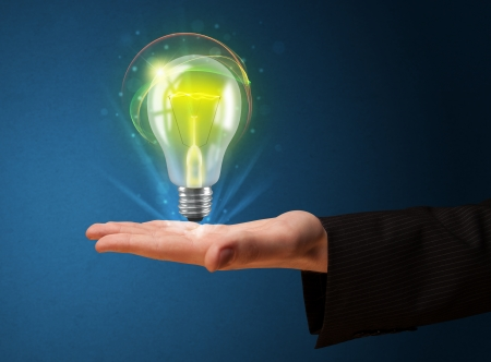 Businessman holding glowing lightbulb in his hand Imagens