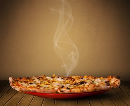 Fresh delicious home cooked pizza with steam on wood deck photo