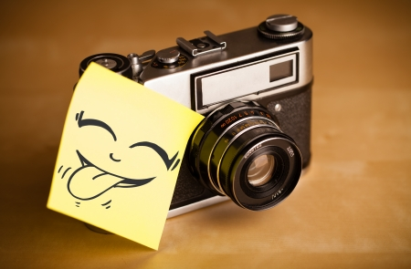 Drawn smiley face on a post-it note sticked on a photo camera photo