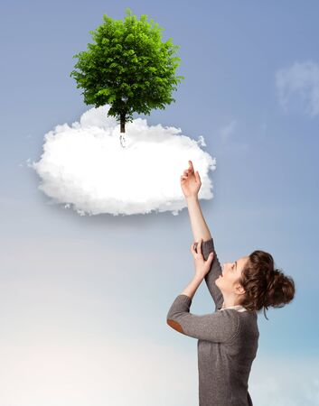 Young girl pointing at a green tree on top of a white cloud concept photo
