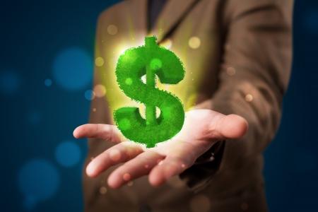 signos de pesos: Joven hombre de negocios en traje de presentar signo de dólar verde brillante Foto de archivo