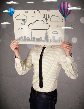 Businessman holding a cardboard in front of his head with cityscape and ballons drawing photo