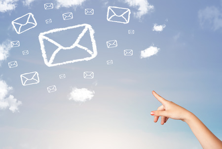 Hand pointing at mail symbol and icon clouds on blue sky photo